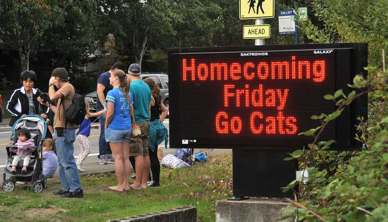 SPOKESMAN PHOTO: VERN UYETAKE  - Parents and students line the streets near the high school waiting for the homecoming parade