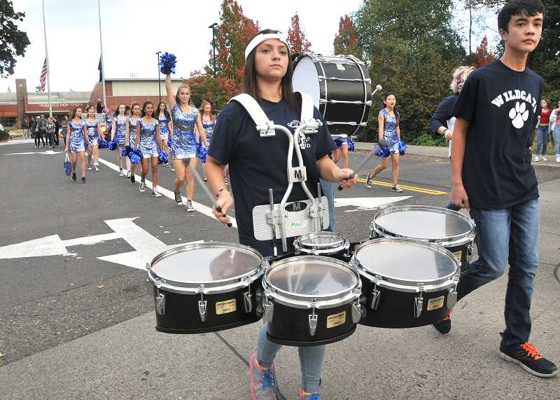 SPOKESMAN PHOTO: VERN UYETAKE  - The Wildcat marching band makes it way out of theschool parking lot.