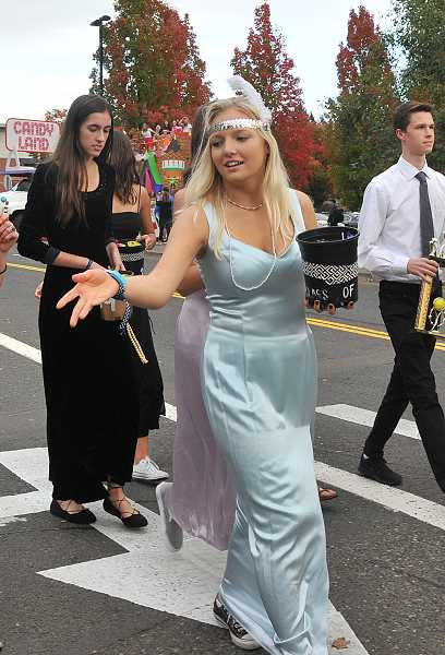 SPOKESMAN PHOTO: VERN UYETAKE  - Junior Hannah Lester throws candy to kids lining the parade route.