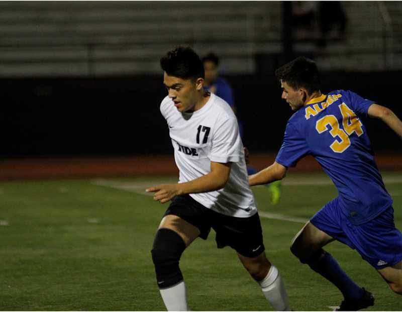 HILLSBORO TRIBUNE PHOTO: WADE EVANSON - Glencoe sophomore forward Kobe Garcia fights for the ball during the Tide's game with Aloha Oct. 5 at Hare Field.