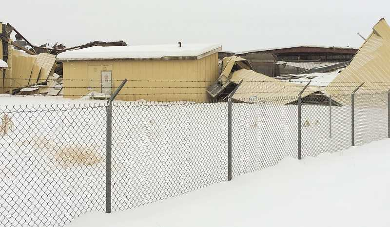 CENTRAL OREGONIAN FILE PHOTO - Heavy snowfall last winter took its toll on the Woodgrain Millwork facility as well as another local business.