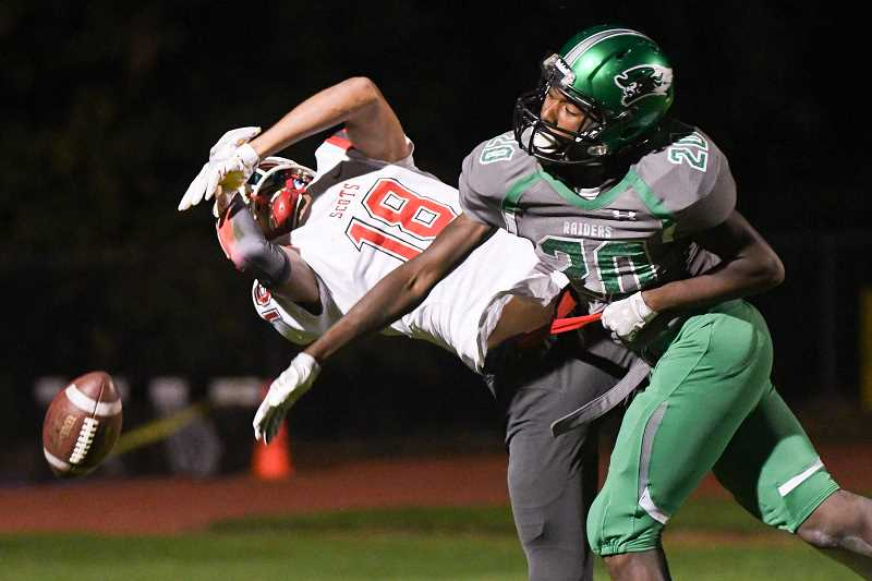 OUTLOOK PHOTO: JOSH KULLA - Reynolds defensive back Dalon Clay knocks away a pass from David Douglas receiver Jaydin Proctor Friday in the Raiders' 42-13 Mount Hood Conference football victory at Mount Hood Community College.