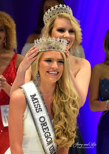 The new Miss Oregon USA, Toneata Morgan, is crowned by last year's winner Elizabeth Denny. Morgan is from Coquille and is a senior at Loyola Marymount University.
