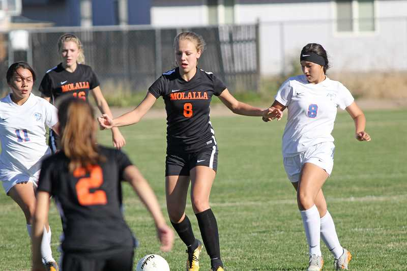 PAMPLIN MEDIA GROUP PHOTO: WILL DENNER  - Molalla sophomore Maddy Lisac (8, black) dribbles the ball down the field in the Indians' 2-0 win over Madras last Thursday.