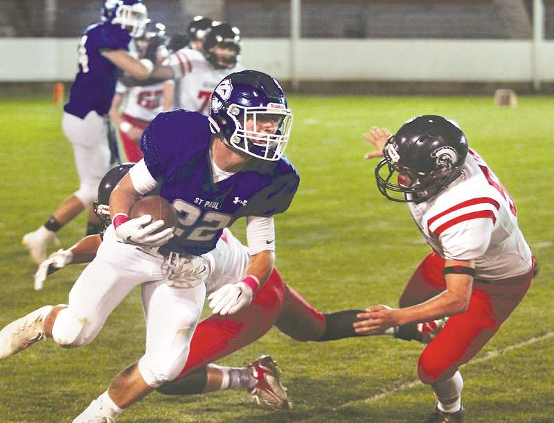PHIL HAWKINS -- WOODBURN INDEPENDENT - St. Paul junior running back Justin Herberger attempts to elude tacklers during the Buckaroos' 54-14 home win over Kennedy Friday night. It was the first time in four attempts that St. Paul beat the rival Trojans.