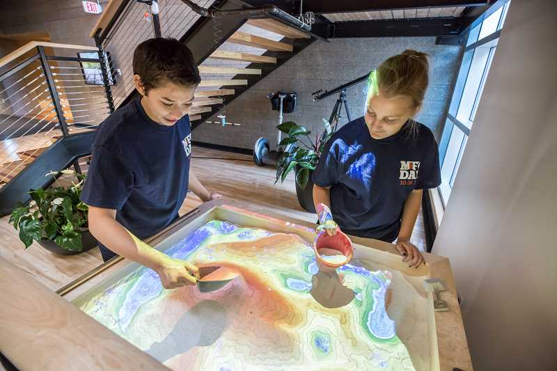 TIMES PHOTO: JONATHAN HOUSE - Southridge students Samantha Travis, left, and Lily Moser check out an Augmented Reality Sandbox during a tour of Vernier for Manufacturing Day.