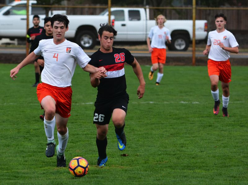 SPOTLIGHT PHOTO: JAKE MCNEAL - Indians senior forward Robby Walsh (4) races Tillamook senior defender Caleb Guerrero (26) to a pass.