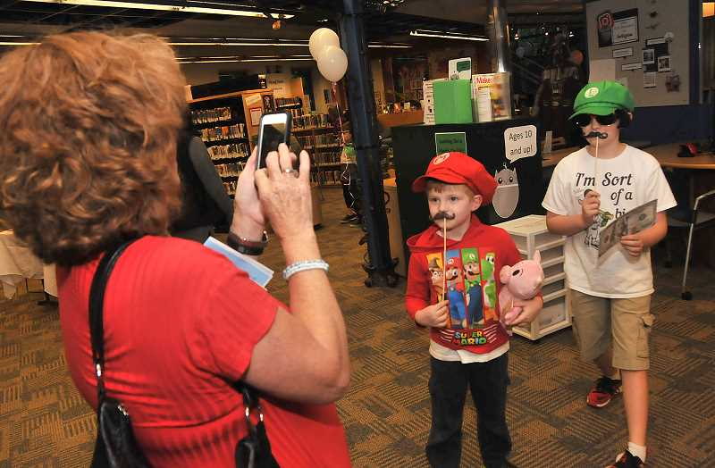 TIDINGS PHOTOS: VERN UYETAKE - Cindy Haldorson takes a picture of her grandsons Brody, left, and Cody Eilers as they dress for the photos booth.