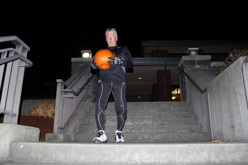 REVIEW PHOTO: SAM STITES - Mike Cavanaugh carries a 10-pound pumpkin as he runs up and down a set of stairs on the campus of Lake Oswego High School during an early morning boot camp session.