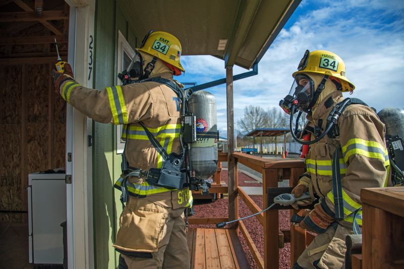COURTESY OF TUALATIN VALLEY FIRE & RESCUE - A team in Level A turnouts test a building for the presence of hazardous gases.