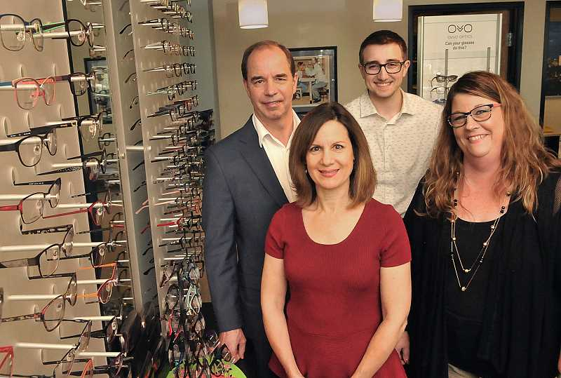 STAFF PHOTOS: VERN UYETAKE  - Shari Mace (from left), Denise Sheerman, Stephen Olsen and Zach Fulps pose by a wall of eyeglass frames at Oswego Optique. Mace has recently joined the firm, working with her husband Stephen Olsen for the first time in their 30-plus-year marriage.