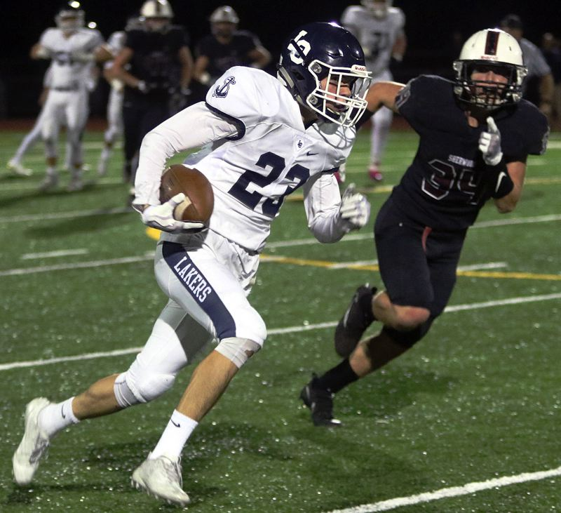 PAMPLIN MEDIA GROUP PHOTO: DAN BROOD - Lake Oswego sophomore Joe Hutson is on his way to scoring on a 60-yard pass play in the Lakers' win at Sherwood.