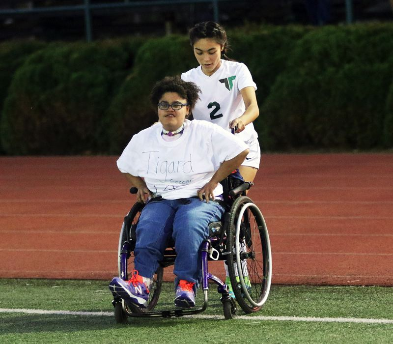 DAN BROOD  - Tigard senior Kyra Medgin and a member of the Tigard High School special needs class take the field prior to the match with Newberg.