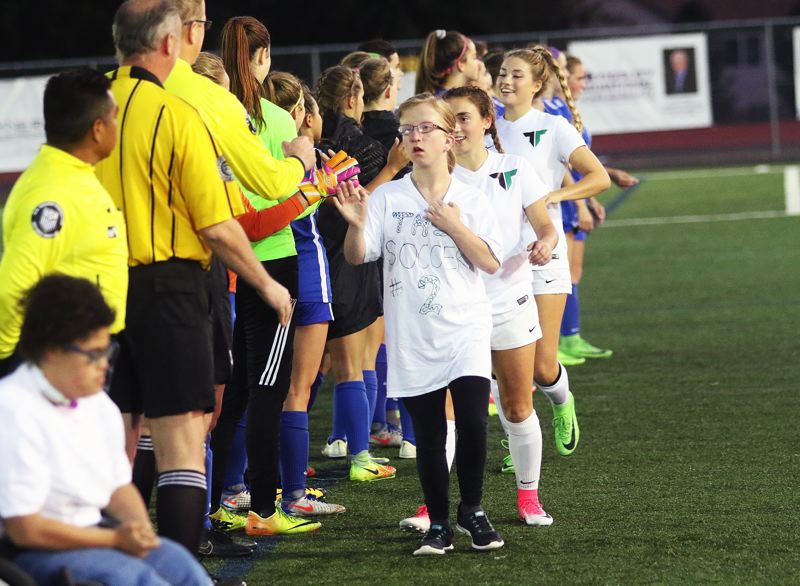 DAN BROOD - Members of the Tigard High School special needs class go through pregame introductions prior to the match with Newberg.