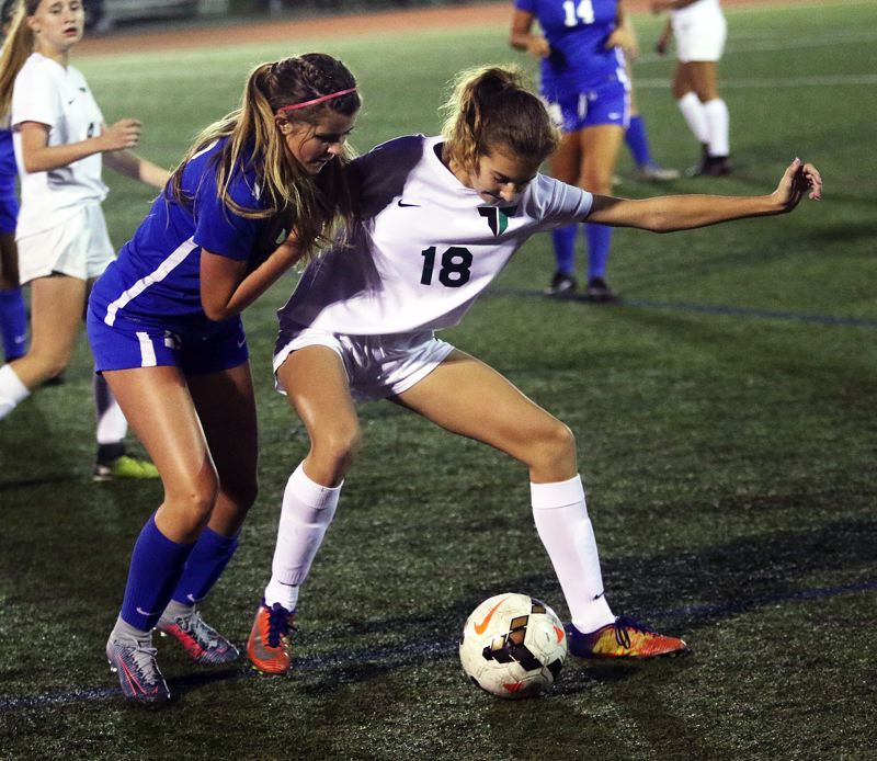 DAN BROOD - Tigard freshman Lydia Emory (18) keeps a Newberg player away from the ball in last week's match.