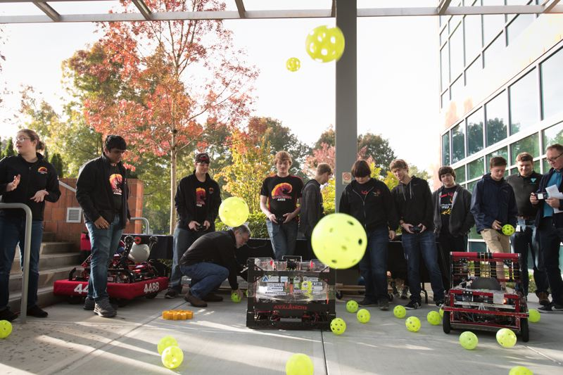 PAMPLIN MEDIA GROUP: JAIME VALDEZ - Members of Shockwave robotics team from Glencoe High School, prepare their robot for a demonstration during Manufacturing Day at Lam Research.Their robot collects whiffle balls and fountains them through the air. The students were at Lam Research in Tualatin to lean about how chip making tools are made. They were part of a Federal push to get teens to explore manufacturing as a career choice, on National Manufacturing Day, October 6.