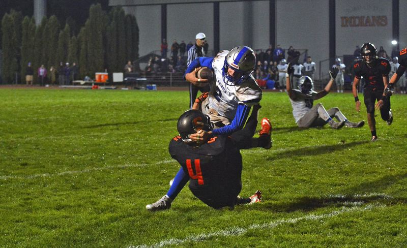 TIMES PHOTO: MATT SINGLEDECKER - Valley Catholic sophomore quarterback Daniel Pruitt runs over a Scappoose defender on his way to the end zone.