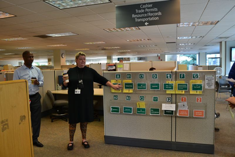 PAMPLIN MEDIA GROUP: JULES ROGERS - Kareen Perkins (seen here and on the cover) is the permitting services section manager at the Bureau of Development Services. David Austin (left) is the BDSs publid information officer. The 12 drop boxes have a camera pointed at them so city staff can pick them up chronologically.