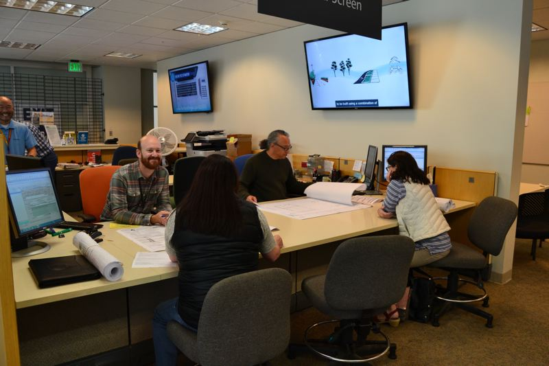 PAMPLIN MEDIA GROUP: JULES ROGERS - Tech II Chris Riley (right) and team leader Matt Weigert (left) look at scale, mechanical plans and life safety with customers.