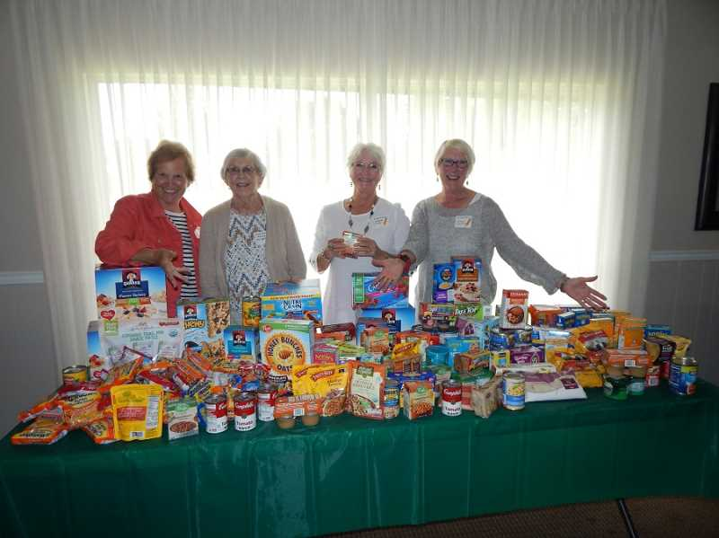 BARBARA SHERMAN - Standing behind some of the food collected by the King City Women's Golf Club for the Tigard Backpack Program are Golf Charity Committee members (from left) Jackie Davison, Mary Norgart, Diana Pliler and Cheryl Carrier.