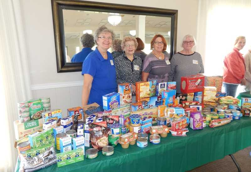 BARBARA SHERMAN - The King City Women's Golf Club's drive to collect food and funds for the Tigard Backpack Program resulted in this display at the luncheon showing half the food collected. Standing behind the food are Golf Charity Committee members (from left) Nancy Skirvin, Margaret Wells, Jan Hall and Janet Craig.