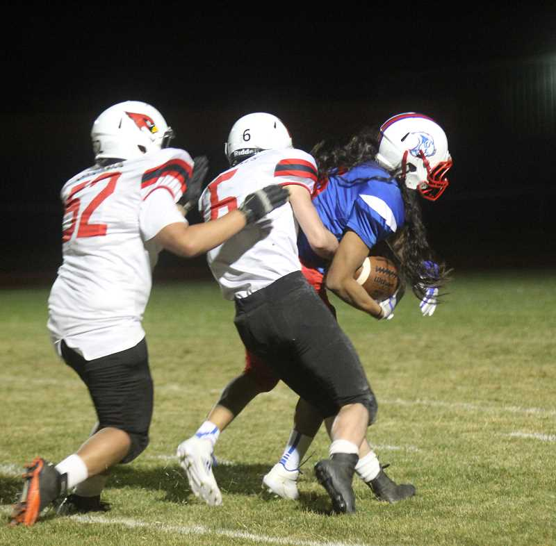 WILL DENNER/MADRAS PIONEER - Catalino LeClaire (right) drags a Corbett defender for a 24-yard gain with under a minute left in the fourth quarter. LeClaire scored a 3-yard touchdown on the next play.