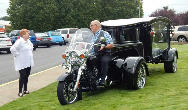 BARBARA SHERMAN - House District 35 Rep. Margaret Doherty (D-Tigard) chats with Ron Threadgill, sitting atop Threadgill Memorial Services' custom-built Harley Davidson motorcyce hearse parked on the lawn in front of the King City Clubhouse.