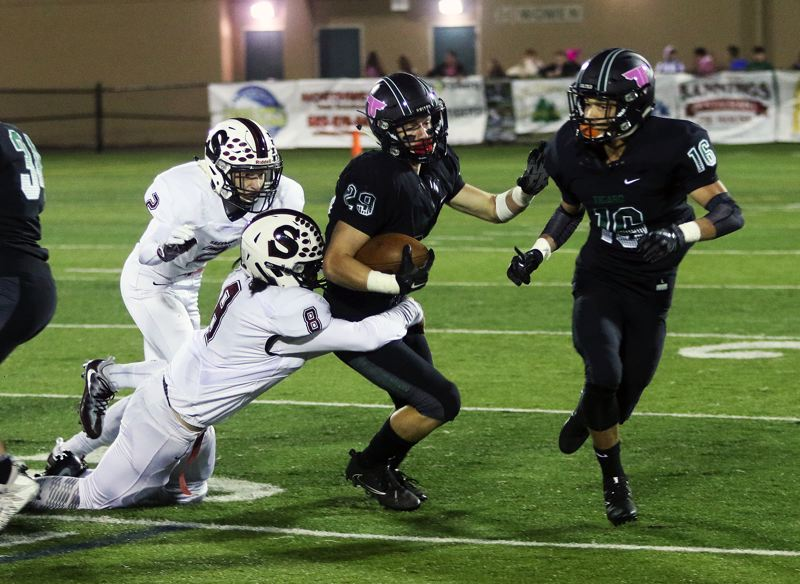 DAN BROOD - Tigard senior Spencer Smith (29) looks to pull away from Sherwood senior Kian Coleman-Lopez in Friday's game.