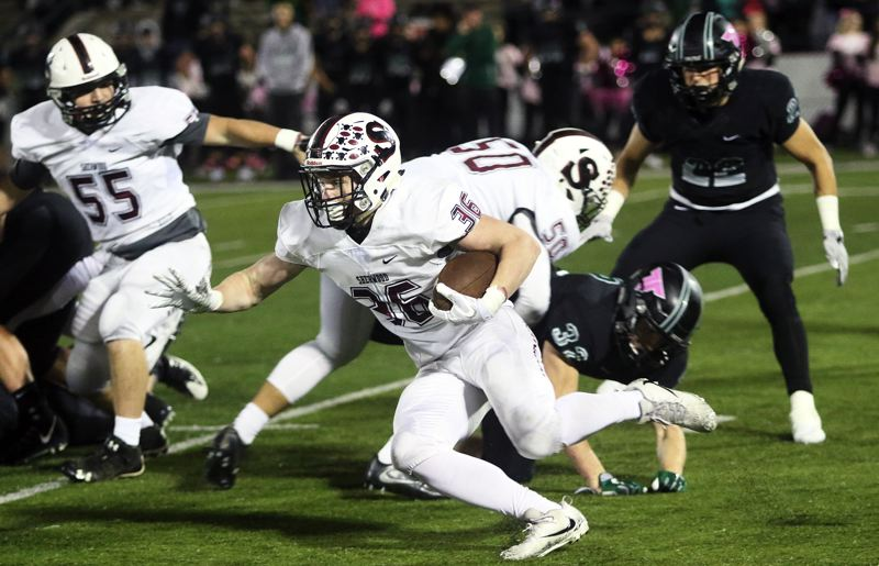 DAN BROOD - Sherwood senior running back Rustin Williams looks to turn the corner during the game at Tigard.