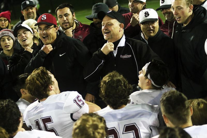 DAN BROOD - Sherwood head coach Greg Lawrence (red cap) and defensive coordinator Wes Montgomery get ready to lead the Bowmen in their victory song following the victory at Tigard.