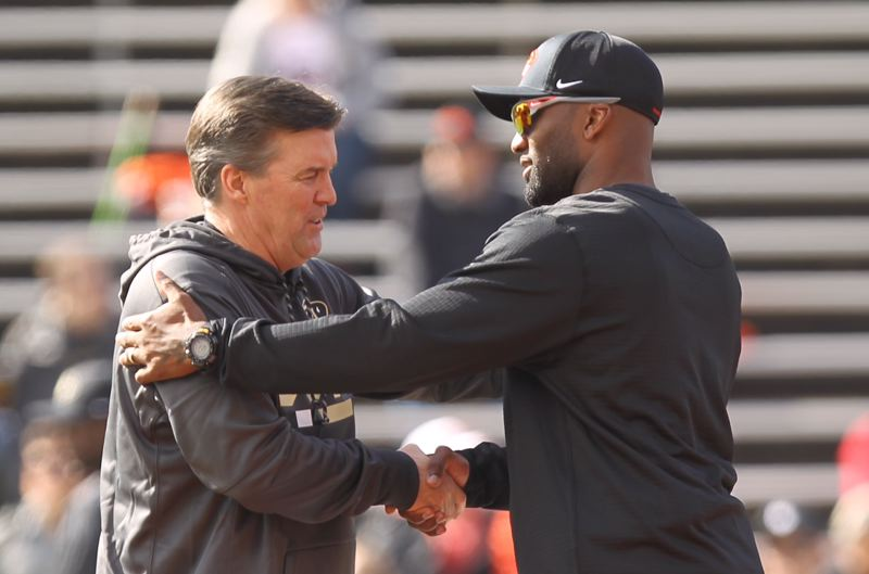 TRIBUNE PHOTO: JAIME VALDEZ - New Oregon State interim coach Cory Hall (right) greets Colorado coach Mike MacIntyre before the Saturday game between the Beavers and Buffaloes at Reser Stadium in Corvallis.