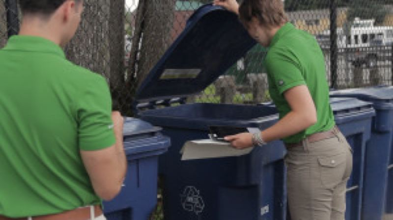 JARED RUSK, KCTVS9/EARTHFIX - Interns Audrey Taber and Crhistian Cuellar examine the contents of the recycling bins at Parkview Apartments in Auburn, Washington to find potential topics for conversation with residents.