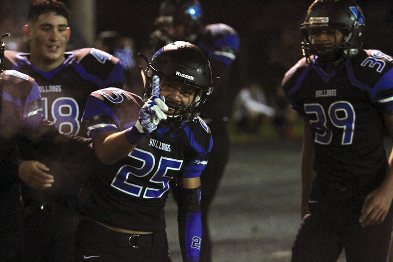 INDEPENDENT PHOTO: PHIL HAWKINS - Woodburn defensive back Jaime Tlatenchi (center) celebrates after his interception set up the Bulldogs'  game-sealing touchdown two plays later during his team's 14-6 home win over the Dalles on Friday.