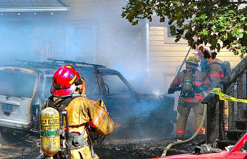 DAVID F. ASHTON - Firefighters spray down a Jeep SUV in the driveway, set aflame by the burning house.