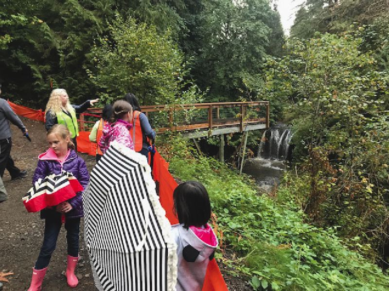 SUBMITTED PHOTO - A group of neighborhood children braved the rain to look at Hidden Falls during the ribbon-cutting event on Sept. 26.