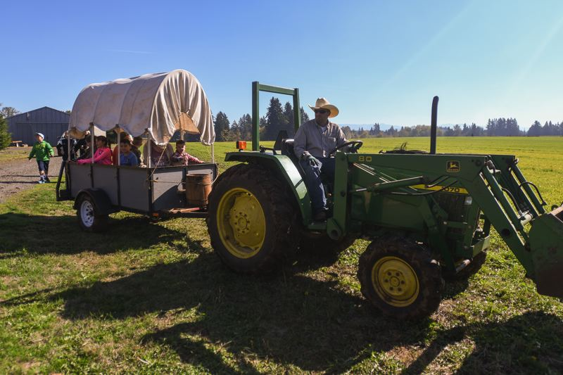 OUTLOOK PHOTO: JOSH KULLA - A hay ride takes off at Dolan Creek Farm Saturday on the opening day of the farm's pumpkin patch.