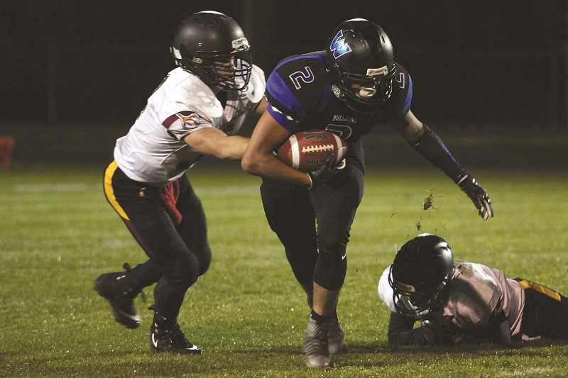PHIL HAWKINS - Woodburn running back Luis Guerrero holds onto the ball as a Riverhawk defender attempts to punch it loose as the Bulldogs held on to win 14-6 and snap a three-game losing streak.