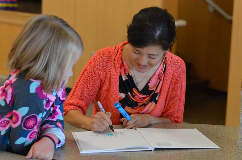 SPOKESMAN PHOTO: CLARA HOWELL - Children's book author, Kathryn Otoshi, signs books after the book reading concludes.