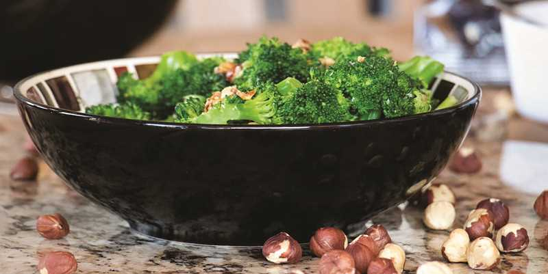 PHOTO COURTESY OF INSP NETWORK - Julie Melcher and her father Dennis helped make a simple dish of broccoli, hazelnuts and garlic for their segment on State Plate, which airs on the INSP network this Friday at 8 p.m.