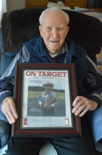 SPOTLIGHT PHOTO: NICOLE THILL - Bob Dudley, 100, of Scappoose, holds a framed photo of himself at age 89 on the cover of On Target Magazine, a publication dedicated to the sport of trapshooting. Dudley celebrates his milestone birthday on Friday, Oct. 20.