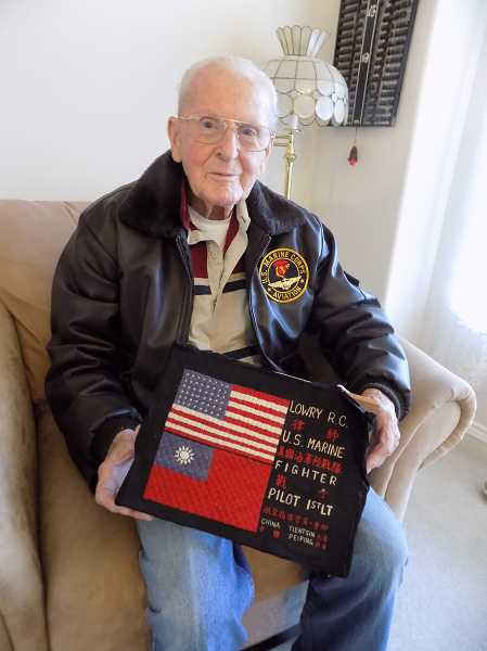 GAZETTE PHOTO: RAY PITZ - Woodhaven resident Rick Lowry holds a so-called blood chit, an embroidered piece of fabric that identified his rank and service history in both English and Chinese, which he had made while stationed in China after the war. Lowry said he hasnt decided yet what hell do on Veterans Day but it will likely be in the company of two war buddies. The city of Sherwood is hosting a Veterans Day ceremony on Saturday, Nov. 11, and the Sherwood Elks Lodge will host a special dinner.