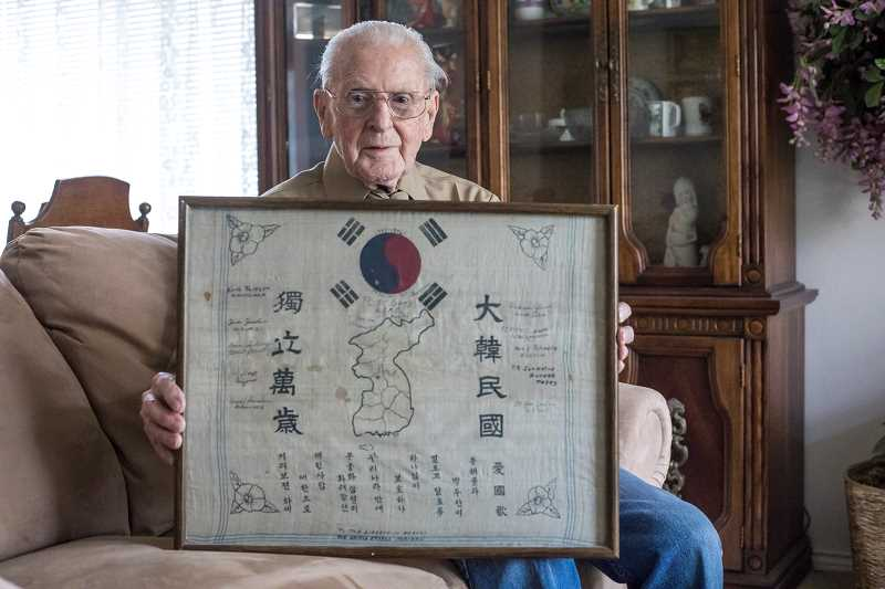 COURTESY RICK LOWRY - World War II veteran Rick Lowry with a print from the people of South Korea, thanking the Americans for their service during the Korean War.