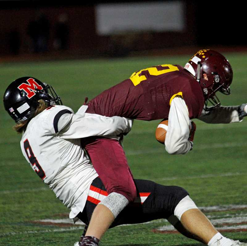 NEWS-TIMES PHOTO: WADE EVANSON - Forest Grove's Cole Hammond fights to break a tackle during the Vikings' game against McMinnville Oct. 20 at Forest Grove High School.