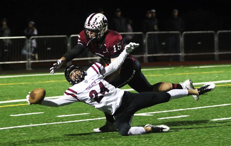 TIMES PHOTO: DAN BROOD - Tualatin's Colby Jackson tries to makea diving catch while defended by Sherwood's Zane Sands during the Timberwolves' 27-12 win over the Bowmen on Friday.