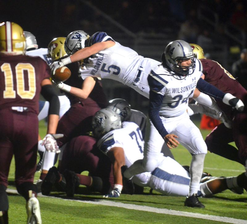SPOKESMAN PHOTO: TANNER RUSS - Wilsonville junior running back Cooper Mootz leaps over the goal line with the ball outstretched for the first score of his team's 49-0 win over Milwaukie on Friday night.