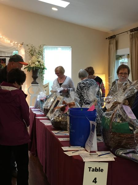 PHOTO BY JERRI ADAMS - Shoppers bid on decorated theme baskets at last years Oregon City Womans Club fundraiser. This years auction is Oct. 29 at the Ainsworth House.
