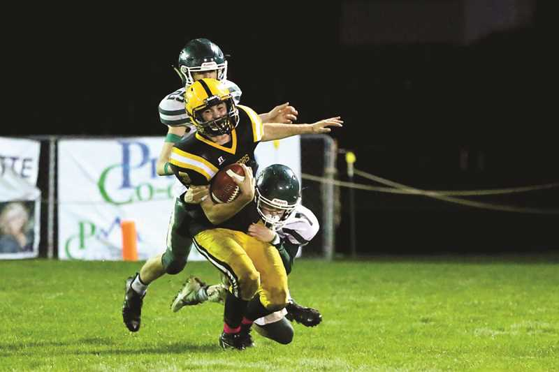 JO WHEAT - North Marion sophomores Brady Hansen and Beau Wilson take down Cascade quarterback Elijah Nolan. The Huskies brought plenty of heat into the Cougar backfield on Friday, scoring a pair of safeties in the 10-0 win.