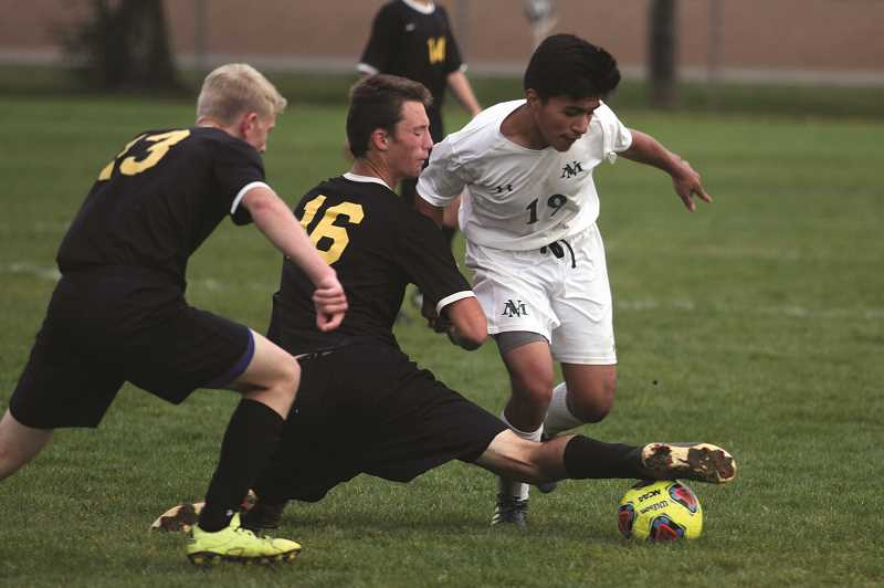 PHIL HAWKINS - North Marion sophomore Rene Ramos attempts to dribble by the Philomath defense in the Huskies' 2-1 victory over the Warriors on Oct. 17. Ramos assisted on the game-winning goal in the 75th minute.