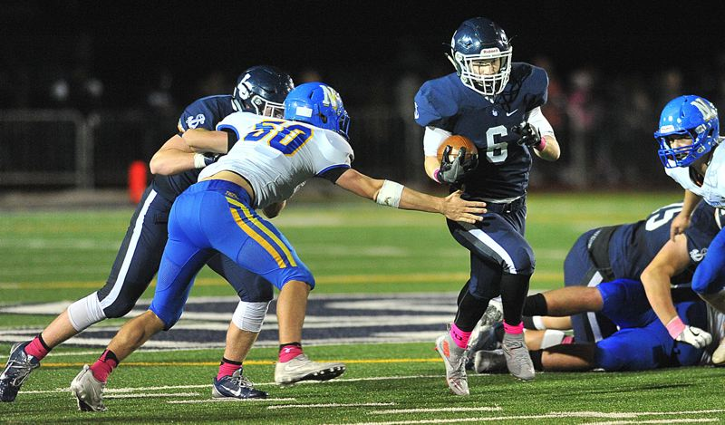 REVIEW PHOTO: VERN UYETAKE - Lake Oswego junior Collin Bracken breaks through the line during his team's 36-7 home win over Newberg on Friday.