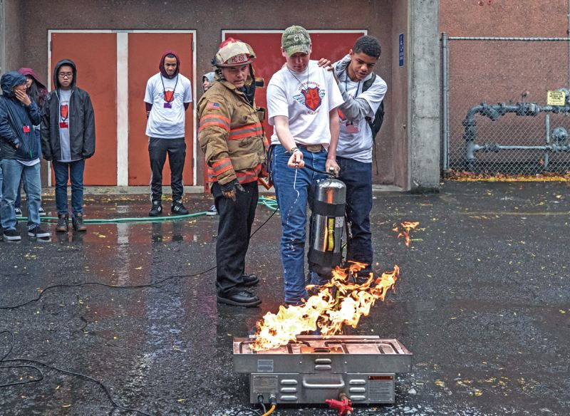 TRIBUNE PHOTO: JONATHAN HOUSE - Benson Tech students Doolan O'Conor, center, and Desmond Acai learn how to put out a fire during the Youth Disaster Academy. Portland Public Schools and its partners put on the academy to boost emergency preparedness — skills that may be more needed for the climate change generation.